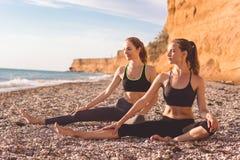 2 девушки делают pilates на пляже Стоковые Фотографии RF