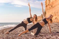 2 девушки делают pilates на пляже Стоковое Изображение
