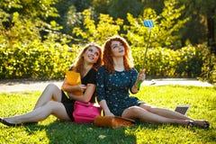 2 девушки делают selfie сидя на лужайке Стоковое Изображение