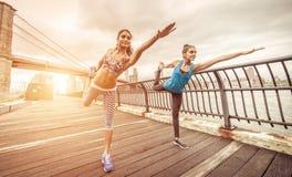 2 девушки делая протягивать в пристани Бруклина на утреннем времени Стоковое Фото