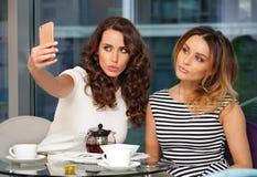 2 девушки делая телефон selfie Стоковая Фотография