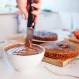 2 девушки делая торт на кухне Женская сливк шоколада stir руки Стоковая Фотография RF