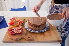 2 девушки делая торт на кухне Руки женщин, причиняя сливк шоколада Стоковые Фото