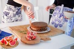 2 девушки делая торт на кухне Women& x27; руки s, причиняя сливк шоколада Стоковое Изображение