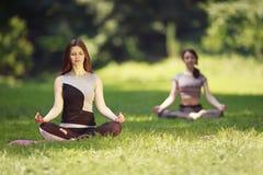 2 девушки делая тренировки йоги в парке Стоковые Фотографии RF