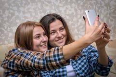 2 девушки делая selfie внутри помещения Стоковое Изображение RF
