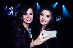 2 девушки делая Selfie на предпосылке партии музыки Стоковая Фотография