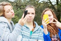 2 девушки делая Selfies одну самостоятельно Стоковая Фотография RF