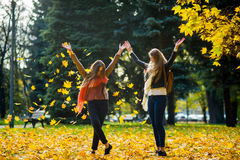2 девушки жизнерадостно тратят время в парке осени Стоковые Изображения