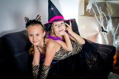 2 девушки замаскированной как тигр и как ведьма ждут так Стоковые Фотографии RF