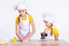 2 девушки замешали тесто, муку, яичко Стоковая Фотография RF