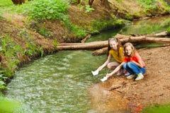 2 девушки запуская бумажные шлюпки от берега реки Стоковая Фотография RF