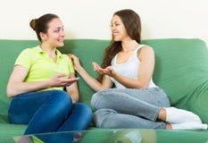 2 девушки злословя на софе дома Стоковое Изображение