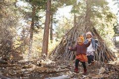2 девушки играют вне укрытия сделанного ветвей в лесе Стоковое Изображение