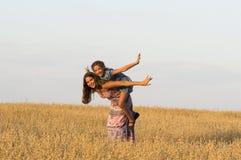 2 девушки играют в поле овса Стоковое Изображение RF
