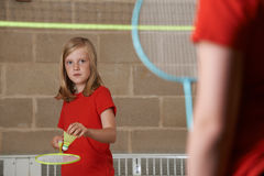 2 девушки играя бадминтон в спортзале школы Стоковое Изображение RF