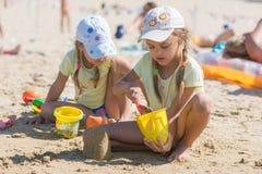2 девушки играя в песке на пляже Стоковая Фотография