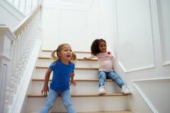 2 девушки играя игру на лестнице дома Стоковое Фото
