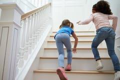 2 девушки играя игру на лестнице дома Стоковая Фотография RF