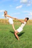 2 девушки играя и работая йогу на луге Стоковое фото RF