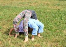 2 девушки играя и работая йогу на луге Стоковая Фотография