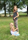 2 девушки играя и стоя на одине другого Стоковые Фото