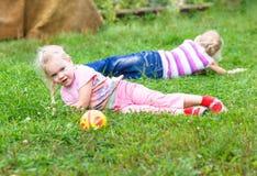2 девушки играя на зеленой траве Стоковые Фото