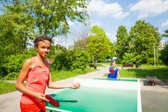 2 девушки играя пингпонг снаружи во время лета Стоковые Фото
