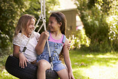 2 девушки играя совместно на качании автошины в саде Стоковое Изображение