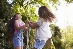 2 девушки играя совместно на качании автошины в саде Стоковое Фото