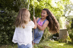 2 девушки играя совместно на качании автошины в саде Стоковые Изображения RF