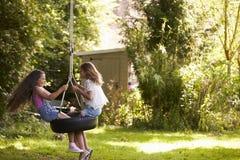 2 девушки играя совместно на качании автошины в саде Стоковое Изображение RF