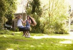 2 девушки играя совместно на качании автошины в саде Стоковая Фотография RF