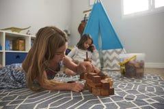 2 девушки играя с строительными блоками в спальне Стоковая Фотография RF
