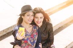 2 девушки играя с телефоном Стоковые Фото