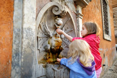 2 девушки играя с фонтаном питьевой воды Стоковая Фотография RF