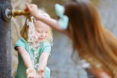 2 девушки играя с фонтаном питьевой воды Стоковое Изображение RF