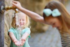2 девушки играя с фонтаном питьевой воды Стоковые Изображения