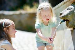 2 девушки играя с фонтаном питьевой воды Стоковое фото RF
