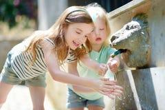 2 девушки играя с фонтаном питьевой воды Стоковое Изображение