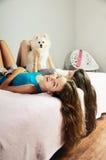 2 девушки играя с Pomeranian на кровати вертикально Стоковое Изображение