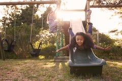 2 девушки играя Outdoors дома на скольжении сада Стоковые Фото