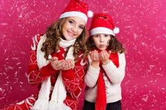 2 девушки имеют потеху с поддельным снегом Стоковые Изображения