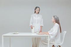 2 девушки имея еду на таблице Стоковая Фотография