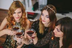 3 девушки имея здравицу для ` s Eve Нового Года, фокуса на девушке Стоковые Фото
