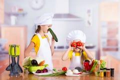 2 девушки имея потеху в кухне Стоковое Изображение