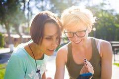 2 девушки имея потеху в парке Стоковое Изображение