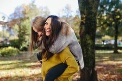 2 девушки имея потеху в парке Стоковые Фотографии RF