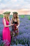 2 девушки имея потеху в поле лаванды Стоковое Фото