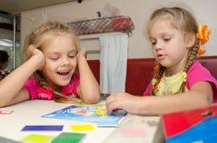 2 девушки имея потеху играя на поезде на таблице на более низком месте в второго класса фуре отсека Стоковое фото RF